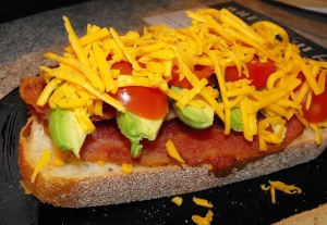 A yummy close up view of all the layers of my bacon, avocado, tomato, cheddar, and black pepper on Toscano bread.