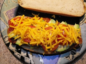 A bacon, avocado, tomato, cheddar, and black pepper on Toscano bread.
