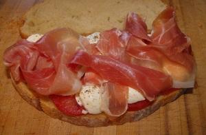 A mozzarella, proscuito, and tomato on Toscano bread.