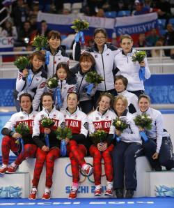 The South Korean team (Gold), top left, the Canadian team (Silver), front left, and the Italian team (Bronze), top and bottom right, pose for photographers during the flower ceremony for the women's 3000m short track speedskating relay final at the Iceberg Skating Palace during the 2014 Winter Olympics.