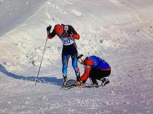 Canadian coach Justin Wadsworth puts on a replacement ski for Russian skier.